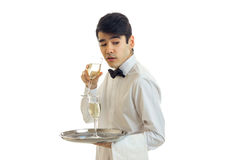Charming waiter in a white shirt holding a glass of wine and wonders. Is isolated on a white background Stock Photography