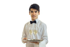 Charming waiter in a white shirt holding a tray with glasses of alcohol. Isolated on white background Royalty Free Stock Images