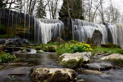 Charming waterfall with spring flowers and stones royalty free stock photos