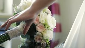 Charming wedding bouquet with glancing diamond lying on the table, then bride in white wedding dress comes up and takes. It. Wedding celebration. Traditions stock video footage
