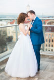 Charming wedding couple holding handes on the terrace with great cityscape Royalty Free Stock Photography