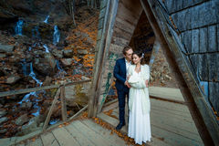 Charming wedding couple kiss on the wooden bridge in mountains. Waterfall background Royalty Free Stock Photography