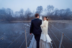 Charming wedding couple walking and holding hands on the suspension bridge. Honeymoon in mountains Stock Photos