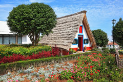 Charming white cottage with a thatched roof gable. Old house-museum of the first settlers on the island of Madeira. Charming white cottage with a thatched roof Royalty Free Stock Photo