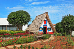Charming white house-museum to Madeira. Charming white cottage with a thatched roof and gable small garden with flowers. Picturesque house-museum of the first Stock Photo