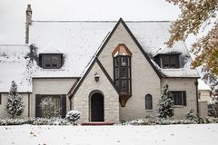 Charming white painted brick cottage with copper accents during snowfall with autumn leaves still on trees.  stock photos