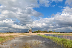 Charming windmill bu river and cblue sky with clouds Royalty Free Stock Photography
