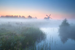 Charming windmill by misty river Royalty Free Stock Image