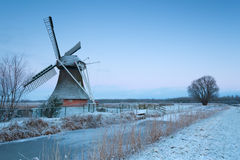 Charming windmill in winter at sunrise Stock Photos