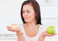Charming woman with an apple and a piece of cake Royalty Free Stock Photo