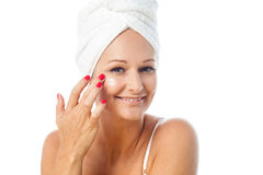 Charming woman applying lotion on her face Royalty Free Stock Photo