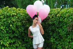 Charming woman with balloons flirting Stock Photos