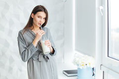 Charming woman in bathrobe drinking milk fom bottle with straw Royalty Free Stock Photos