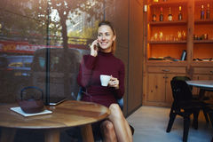 Charming woman with beautiful smile having pleasant conversation on cell telephone while resting after work Stock Photos