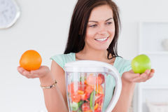 Charming woman with a blender and fruits Stock Photos