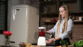 Charming woman blending beet smoothie with blender stock footage
