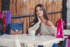 Charming woman in a cafe for a cup of coffee. Young beautiful brunette woman with long straight hair and brown eyes, after an exhausting shopping with colored Royalty Free Stock Photo