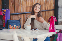 Charming woman in a cafe for a cup of coffee. Young beautiful brunette woman with long straight hair and brown eyes, after an exhausting shopping with colored Stock Photography