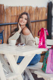 Charming woman in a cafe for a cup of coffee. Young beautiful brunette woman with long straight hair and brown eyes, after an exhausting shopping with colored Stock Photos