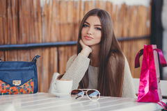 Charming woman in a cafe for a cup of coffee. Young beautiful brunette woman with long straight hair and brown eyes, after an exhausting shopping with colored Royalty Free Stock Photos