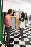 Charming woman checking the price of the beige blazer. Checking a price. Charming stylish attractive alluring dazzling long-haired nice-looking women checking stock photos