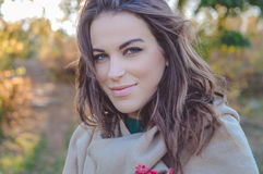 Charming woman in coat gently smiling on autumn Royalty Free Stock Photo