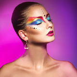 Charming woman with colorful make up on purple background Royalty Free Stock Photos