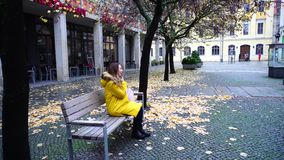 Charming woman communicates on cell phone and strolls through autumn city in open air. Fine girl talks on phone and goes to wooden bench, sits down and reports stock footage