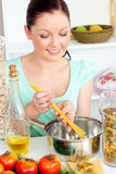 Charming woman cooking sphaghetti in the kitchen. At home Stock Photo