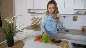 Charming woman cooks phone in hands and composes composition of vegetables for photo, standing in middle of stylish. Nice girl takes photo on mobile and displays stock footage