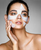 Charming woman with cotton facial mask. Portrait of beautiful young brunette touching hand her face. Skin care concept Royalty Free Stock Photos