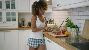 Charming woman dancing while preparing food stock footage