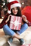 Charming woman with dark hair posing near Christmas tree. Fashion studio photo of beautiful charming woman with dark hair in warm cozy winter clothes posing near Royalty Free Stock Photo