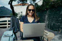 Charming woman designer in sunglasses working with laptop in out Stock Photo