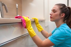 Charming woman doing cleaning. House cleaning. Side view - woman - employee of cleaning company in rubber gloves wiping furniture from dust royalty free stock image