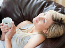 Charming woman drinking coffee sitting on a sofa Royalty Free Stock Photography