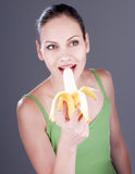 Charming woman eating a banana. Royalty Free Stock Images