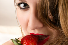 Charming woman eating strawberry royalty free stock photos
