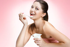 Charming woman eating yogurt Stock Image