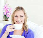 Charming woman enjoying her coffee on the sofa Stock Photography