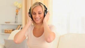 Charming woman enjoying some music stock footage