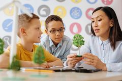 Charming woman explaining the notion of photosynthesis to schoolchildren. Key principles. Beautiful young teacher explaining the notion of photosynthesis to her royalty free stock images