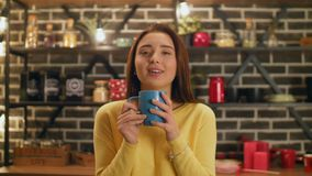 Charming woman enjoying aroma of coffee in kitchen stock video footage