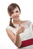 Charming woman giving a thumbs up. Charming young woman with a gentle smile giving a thumbs up of approval and hope as she looks down at the camera, isolated on Stock Images