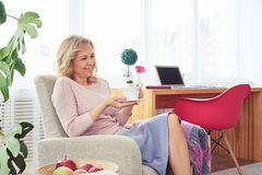 Charming woman having rest with cup of coffee in armchair after Stock Images