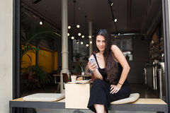 Charming woman holding her smart phone and look at the camera while sitting in modern coffee shop outdoors. Beautiful female read good news on the cell telephone Royalty Free Stock Images