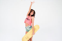 Charming woman holding skateboard and showing peace sign Stock Images