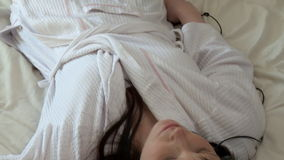 Charming woman listening music lying on bed stock footage
