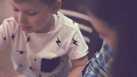 Charming Woman And Little Boy Doing Homework. Beautiful Young Mother In Plaid Blue Shirt Smiles And Her Little Curious Son Doing Homework Sitting At The Table stock footage