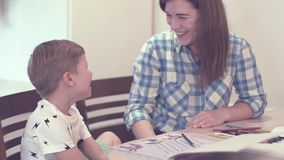 Charming woman and little boy doing homework. Beautiful young mother in plaid blue shirt smiles and says something to her little curious blurred son while doing stock video footage